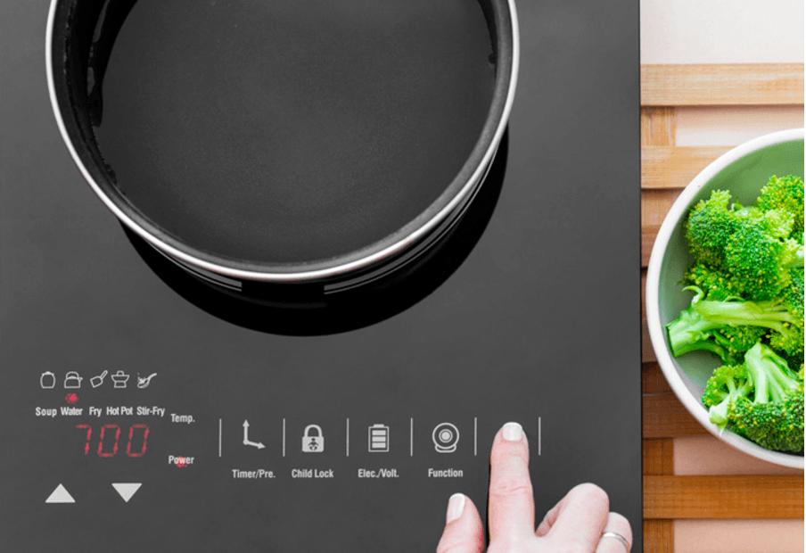 Vrouw die een energiezuinige inductie fornuis aanzet. tip: een inductiefornuis is zuiniger dan een elektrische kookplaat.