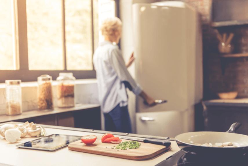 Vrouw die energiezuinige koelkast opentrekt. Koelkast sluiten is belangrijk tegen sluipverbruik.