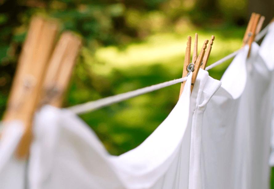 Witte lakens aan de wasdraad. Tip: hang je was aan de wasdraad om energie te besparen.
