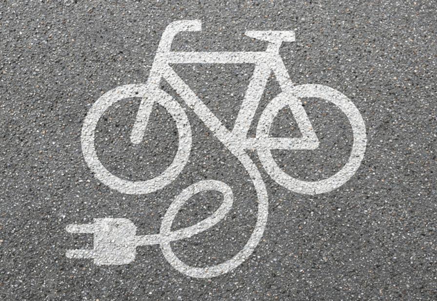 Krijttekening van fiets met stekker. Elektrische fietsen verbruiken, maar zijn energiezuiniger dan wagens.