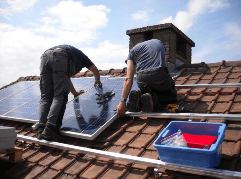 Werklieden die zonnepanelen plaatsen. Zonnepanelen zijn essentieel om energie te besparen.